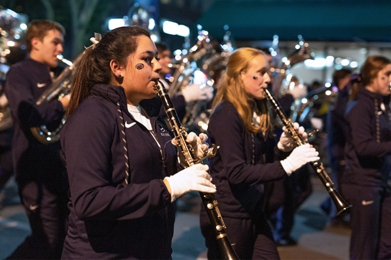 Blue band members march and play their clarinets during the Penn State homecoming parade.