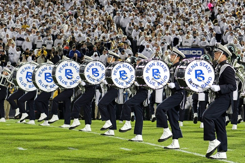 The blue band drum line marches in perfect sync across the field during a white out night game halftime performance.