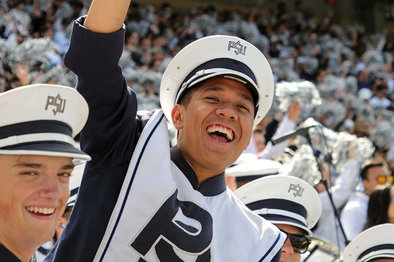 During college game day, a blue band member cheers in the stands during the football game.