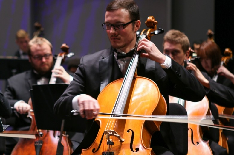 Cellists performing in an orchestra, bow-hand and bow of the foreground player blurred with movement.