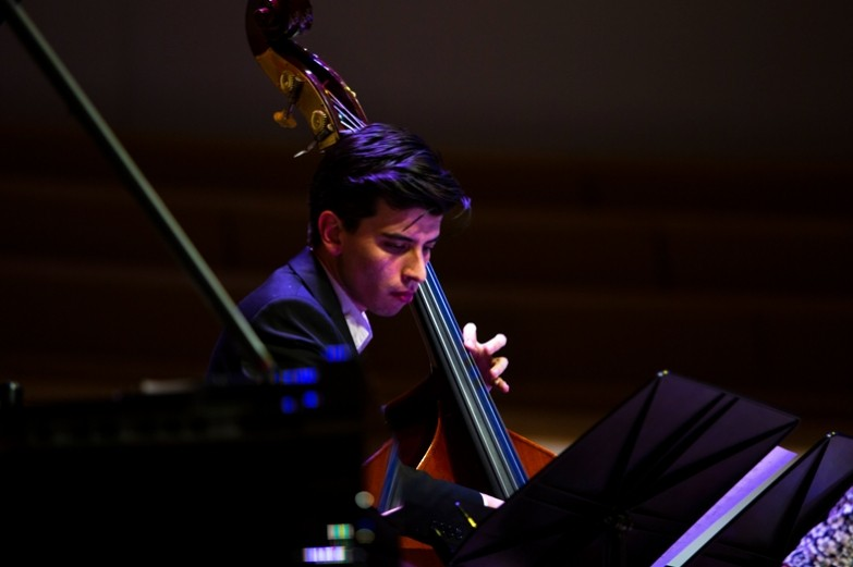Cellist, seated behind piano and music stands playing.