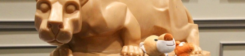 Cropped replica of Nittany Lion statue with cute, plush, stuffed lion toys.