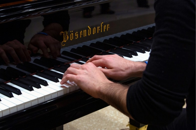 Closeup of hands, with fingers poise on the keys of a Bosendorfer grand piano
