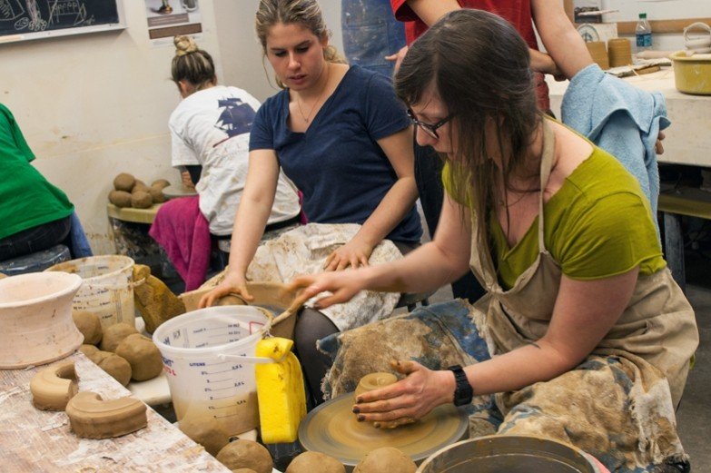 Students literally up to their elbows in clay while wheel throwing pottery in the School of Visual Arts ceramics studio.