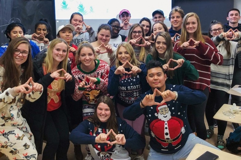 Close to two dozen Stuckeman School students clustered together holding their fingers up in diamond shapes in support of Penn State's THON event to fight pediatric cancer.