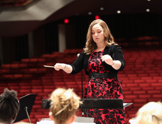 A Penn State School of Music student conducts an ensemble of elementary school students during a pre-researsal of the tenth anniversary Partners in Music concert held at Eisenhower Auditorium.