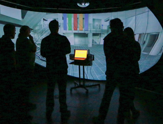A group of researchers standing in a darkened room engaging with a virtual environment projection
