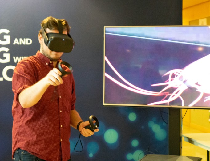 A student wearing VR goggles and holding two hand controllers while engaging with a virtual environment