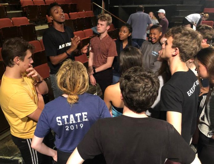 Musical theatre summer campers gathered around an instructor in Penn State's Pavilion Theatre.