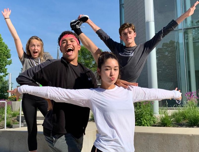Four STATE musical theatre summer camp participants striking poses for a group photo by Penn State's Recital Hall.
