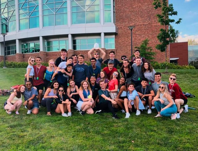 Smiling and laughing STATE musical theatre summer camp participants posing for a group photo on a green lawn on campus.