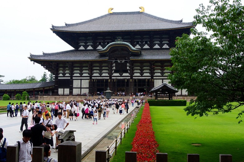 Tourists walking in an open space in front of a public landmark in East Asia.