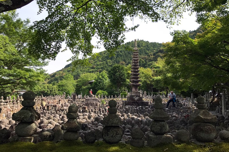 Area of architectural sculptures and rocks surrounded by nature in East Asia.