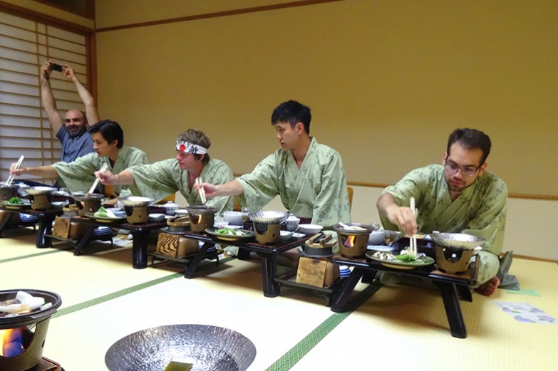 Penn State students sit in a row on the floor eating an authentic korean meal with chopsticks.