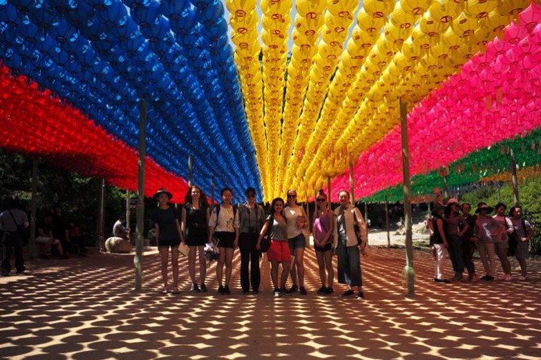 A group of Penn State students stand together to get their picture taken under rows and rows of vibrant lanterns at Seokguram Grotto.