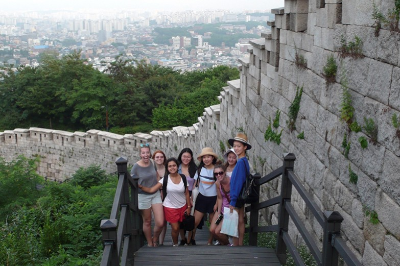 A group of Penn State students stand together for a picture at the Seoul City Wall.