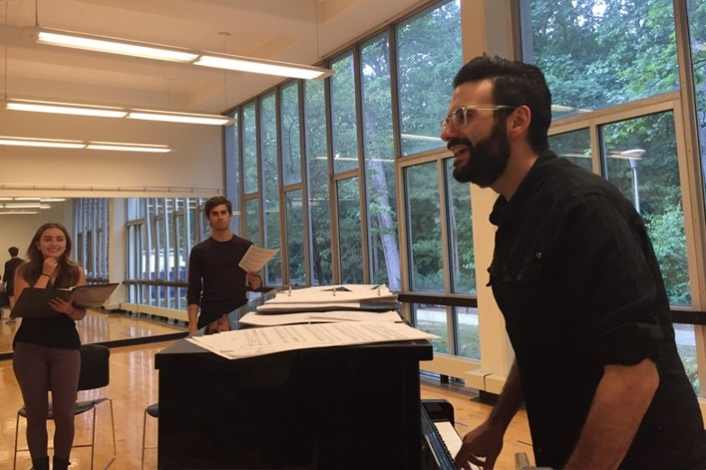 Joe Iconis stands at the piano while students rehearse in the studio