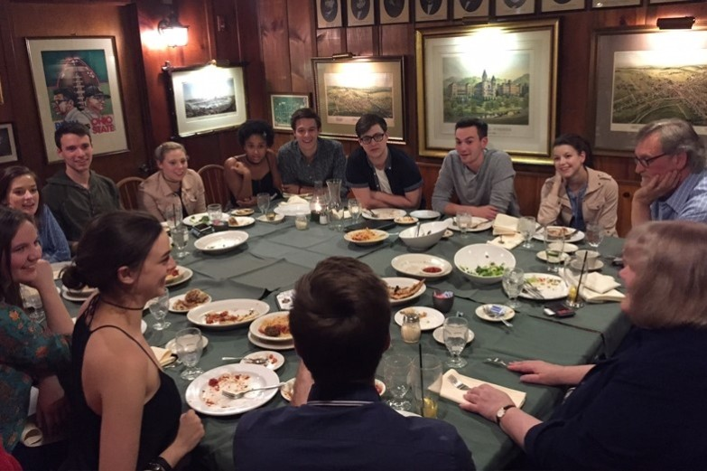 Musical Theatre students sit around a large dining table during a discussion with Mike Reid and Sarah Schlesinger