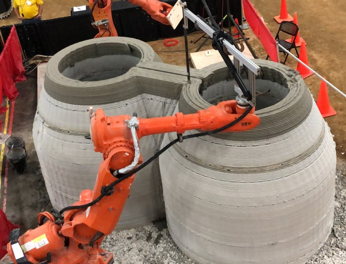 Orange multi-axis industrial CNC robots being used for 3d-printing concrete forms.