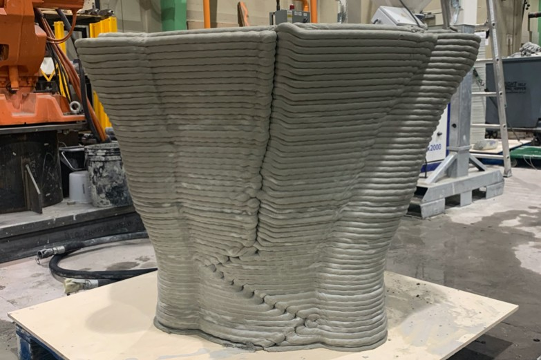 Exterior of 3d-printed hollow concrete form, showing hundreds of stacked layers of printed concrete.