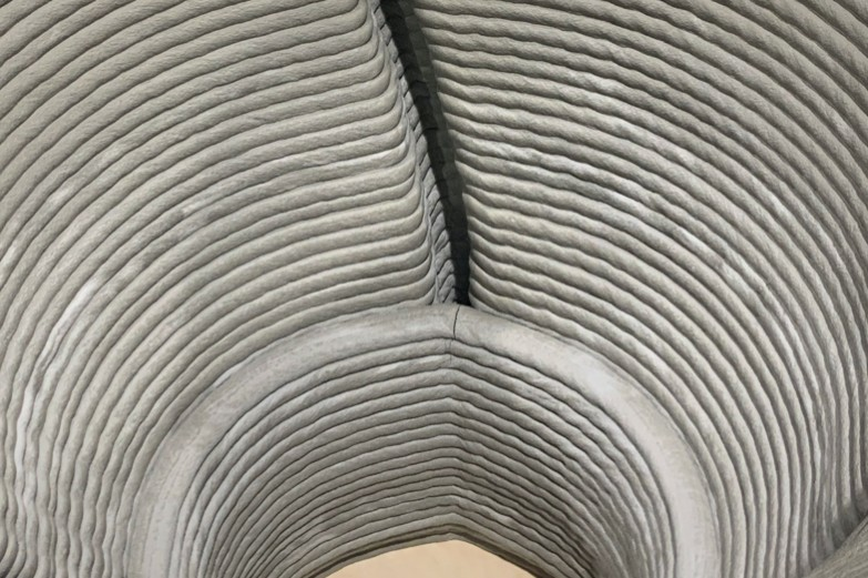 Interior close-up of 3d-printed hollow concrete form, showing stacked, offset layers of printed concrete.