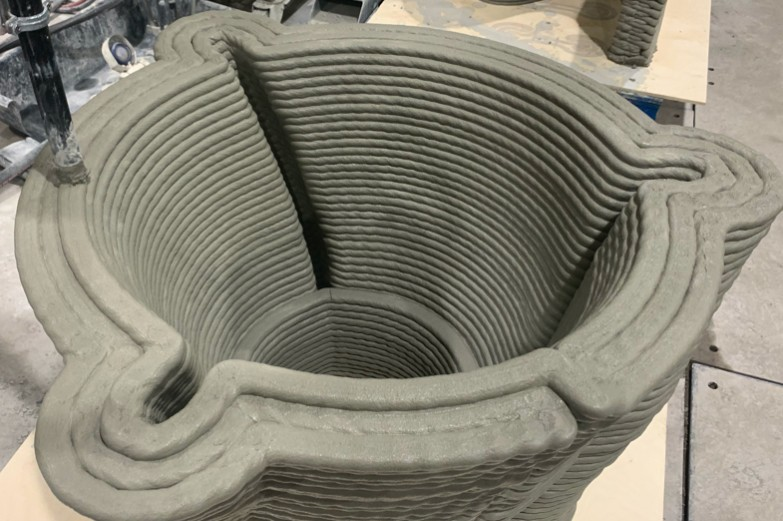 Interior of 3d-printed hollow concrete form, showing stacked, offset layers of printed concrete.
