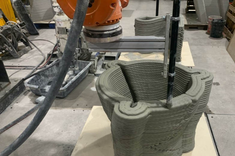 Overhead view of ABB industrial robot 3d-printing a large hollow concrete form.