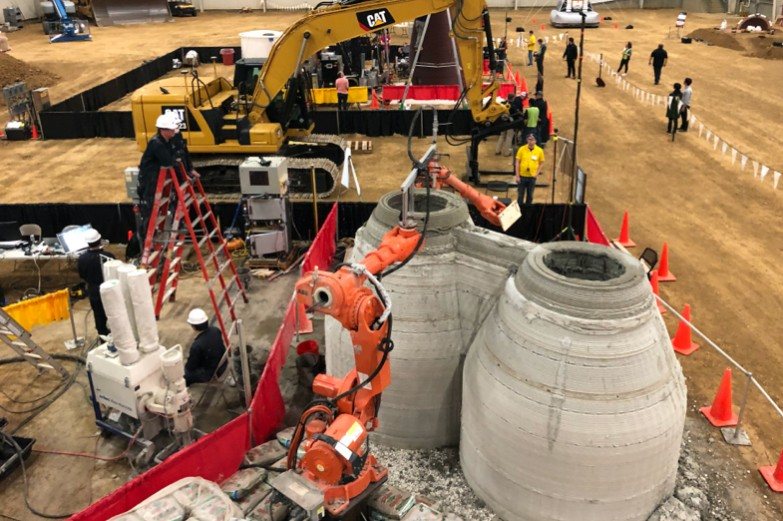 Inside a huge warehouse, large Caterpillar excavator equipment lifts industrial robots into place to make scale models of human-habitable enclosures from printed concrete.