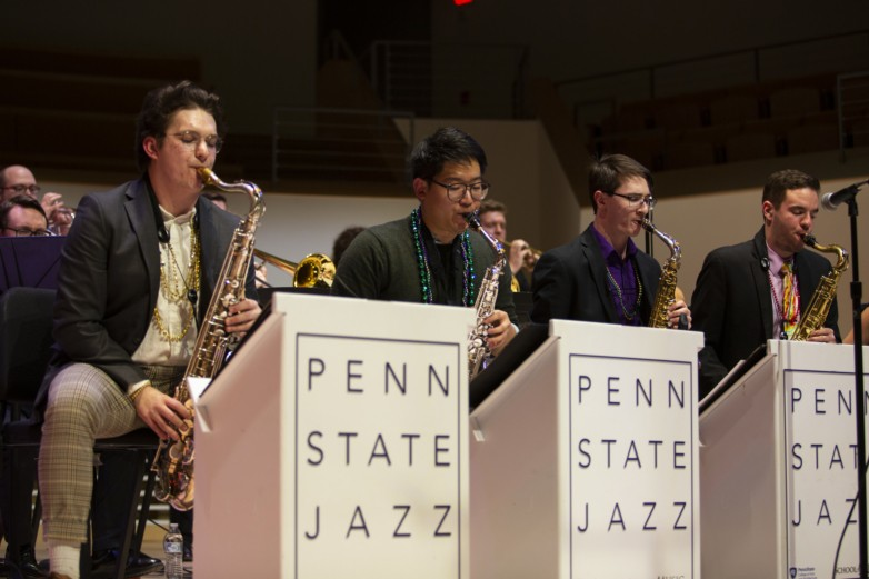 Group of four School of Music students playing the saxophone during a jazz performance, behind a row of Penn State Jazz podiums.