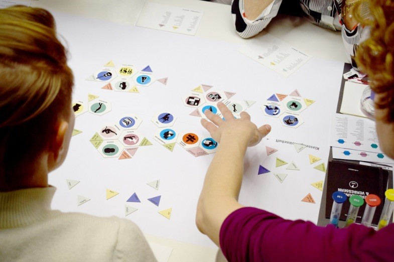 Overhead view of young students moving game pieces on table. A participatory design game for school design, developed by Baupiloten, Berlin.