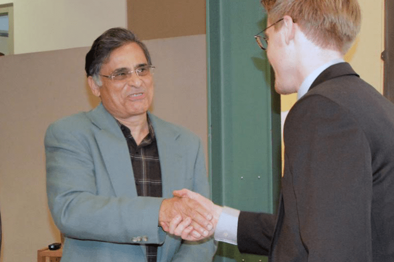 Jawaid Haider shaking the hand of a student.