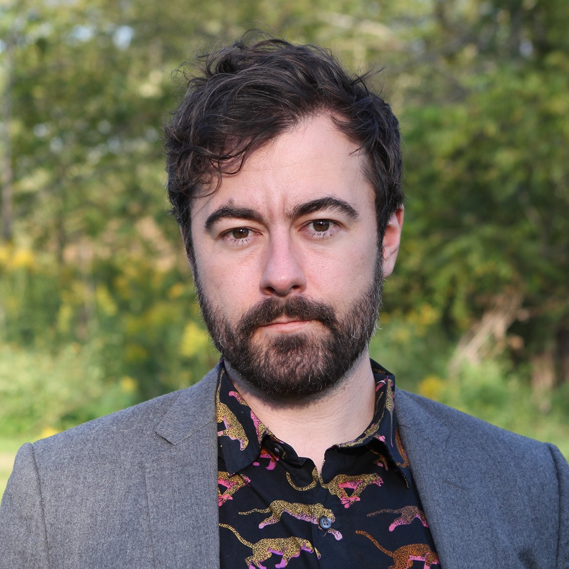 headshot of art history professor wearing patterned black shirt and gray jacket