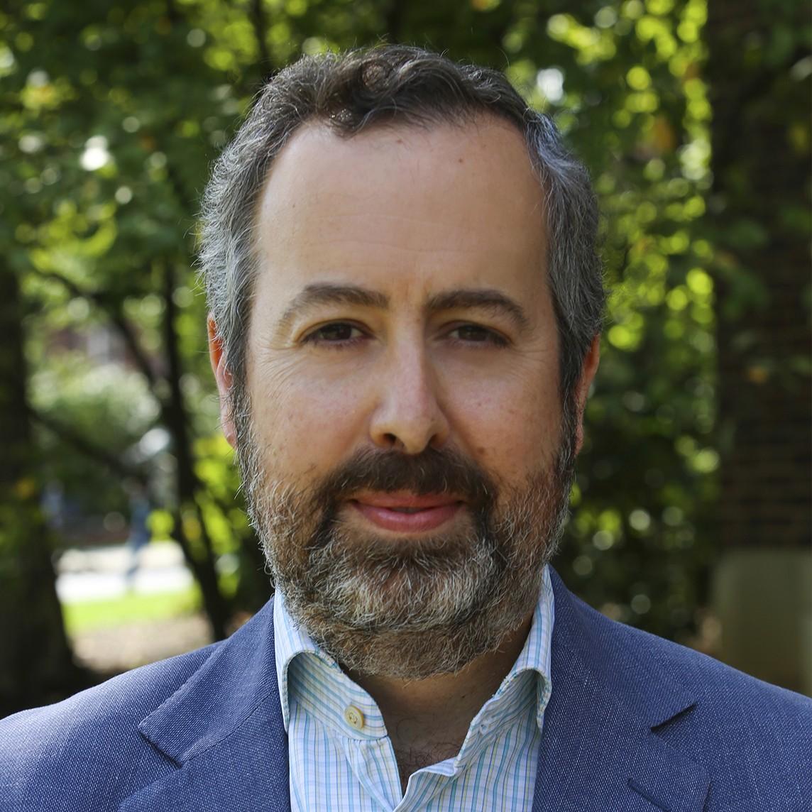 Headshot of Professor Robin Thomas wearing plan shirt and blue jacket